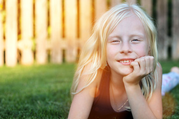 beautiful blonde smiling  girl  lying  on the grass on a summer day