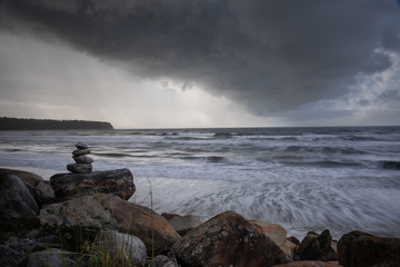 Balanced stone stacks against a stormy seascape