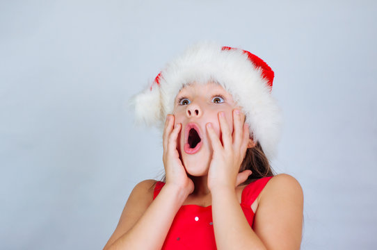 little cute girl is standing in a Christmas hat and surprised at the holiday