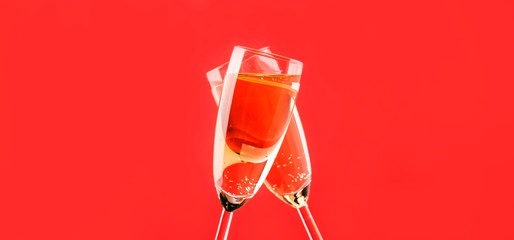 Two champagne flutes make cheers on red light bokeh background banner