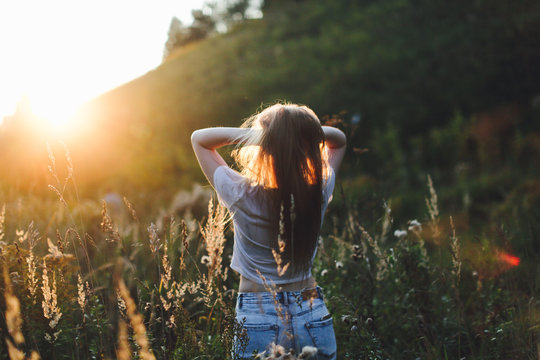 caucasian girl with long hair in field at sunset