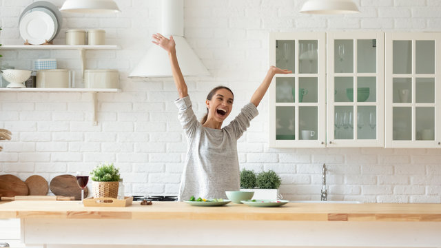 Overjoyed young woman raise hands feel excited cooking in kitchen