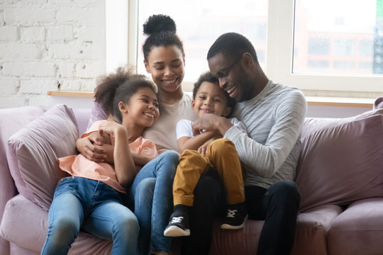 Happy biracial family with kids relax on cozy sofa