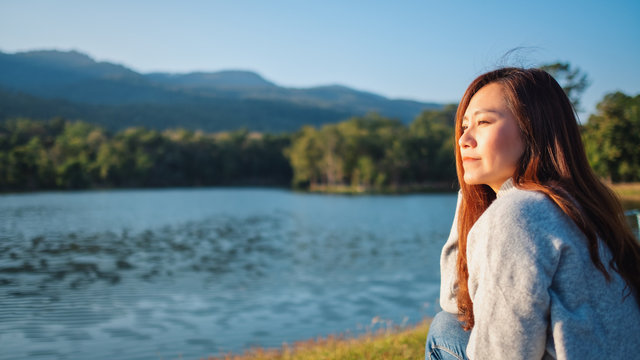 Portrait image of a beautiful asian woman sitting in front of the lake and mountains before sunset