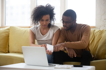 Biracial couple sit on couch managing finances paying bills Wall mural