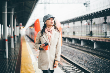 Pretty woman holding red cup and enjoying coffee during waiting the train at the station. Girl Enjoying winter morning under the snowfall with hot drinks and listening to music on headphones.