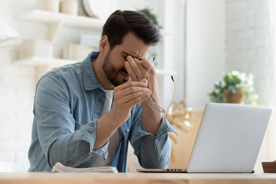 Tired young man feel eyestrain holding glasses fatigued from computer
