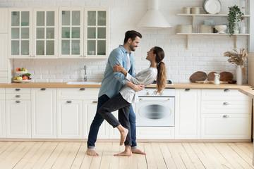 Fototapeta Happy romantic couple dancing in modern kitchen at home obraz