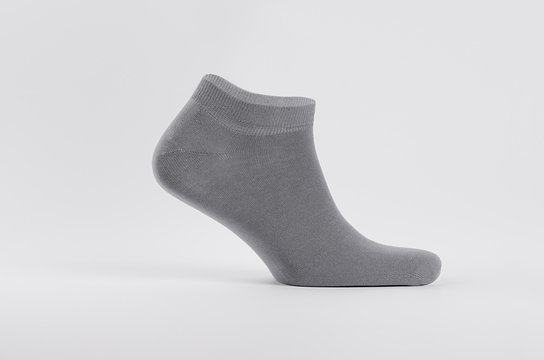 Blank grey cotton short sock on invisible  foot on white background as mock up for advertising, branding, design, side view, template.