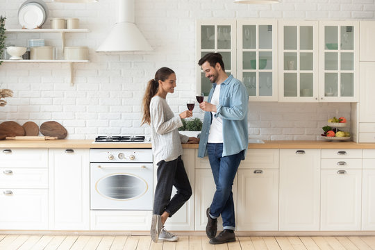 Romantic affectionate young couple drinking wine standing in modern kitchen