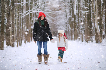 A winter fairy tale,in the forest. A girl on a sled with gifts on the eve of the new year in the park. Two sisters walk in a New Year's park and ride a sled with gifts.