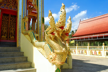 The three-headed serpent statue is made of gold painted cement.;
