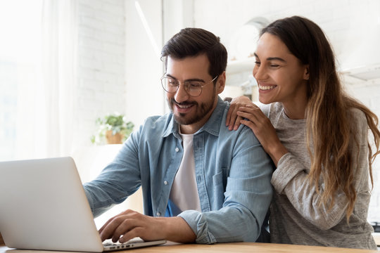 Smiling millennial couple using laptop looking at screen at home