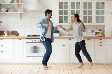 Happy active young couple husband and wife dancing in kitchen