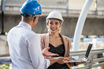 Young American beautiful female engineer with helmet dicsuss construction project with his manager by using laptop computer. Happy teamwork to achieve goal at site building in modern city.
