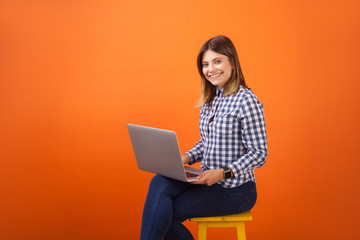 Portrait of positive young woman with brown hair in checkered casual shirt and denim sitting with toothy smile, working on laptop, looking at camera. indoor studio shot isolated on orange background