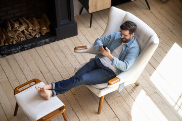 Relaxed guy sit on comfortable chair in house using phone