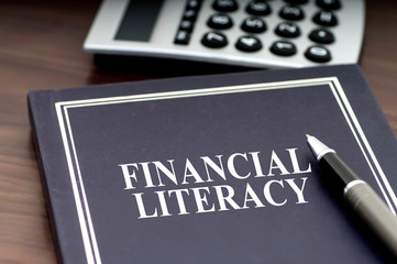 Financial Literacy book with pen and calculator