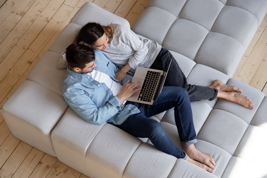 Happy young couple using laptop relaxing on sofa, top view