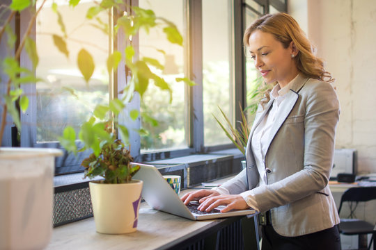 Mature businesswoman standing near windows and using laptop in modern office
