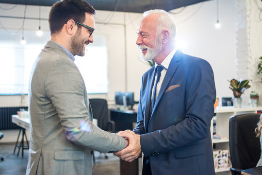 Senior executive shaking hands with young employee at office