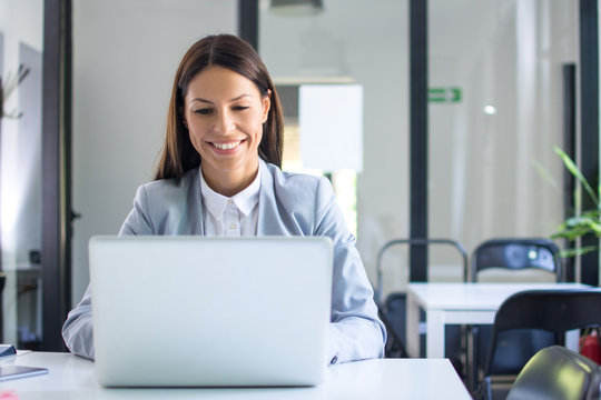 Beautiful young businesswoman in formal wear using laptop in office