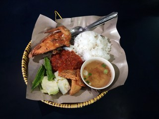 Popular food among Malaysian called (Nasi Ayam Penyet) rice served with fried chiken, fermented soybean call Tempe, spicy sauce, vegetables and hot sup. Original dish from Indonisia. Black background.