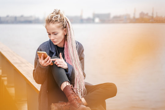 Stylish beautiful young blonde girl with pink dreadlocks in a coat on a gray autumn day in the city with a smartphone in her hands