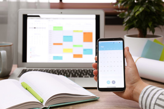 Woman holding smartphone with calendar app at table, closeup