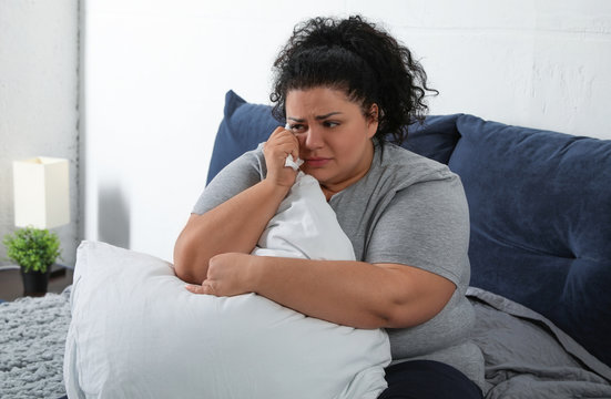 Depressed overweight woman crying while hugging pillow on bed