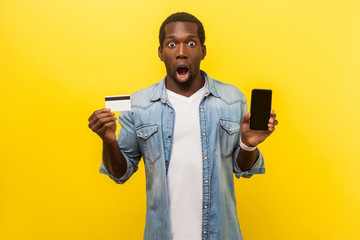 E-commerce. Portrait of surprised amazed man in denim casual shirt holding plastic bank card and phone, shocked by quick electronic money transfers. indoor studio shot isolated on yellow background