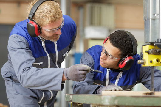 young manual worker wearing protective clothing in metal industry