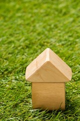 Little wooden miniature house model on green grass background with copy space - ecological living or house building concept - fototapety na wymiar