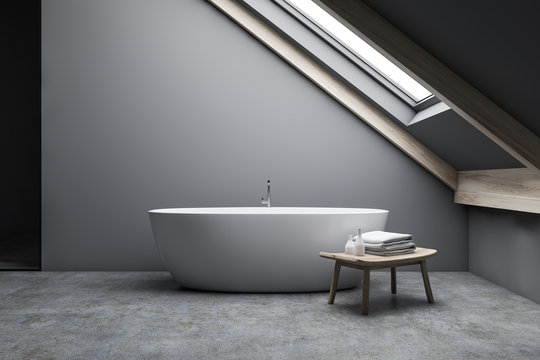 Attic gray bathroom interior with tub and bench