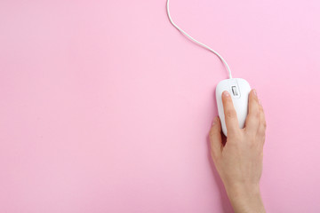 Woman using modern wired optical mouse on pink background, top view. Space for text