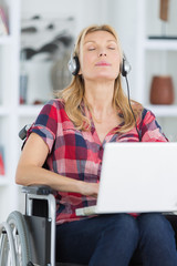 happy woman in wheelchair listening to music