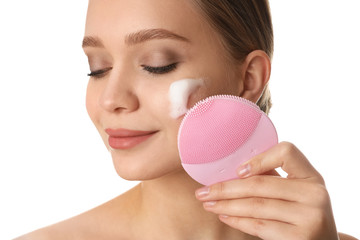 Fototapeta Young woman washing face with brush and cleansing foam on white background. Cosmetic products obraz