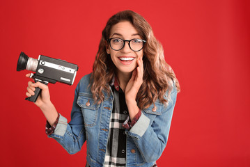 Beautiful young woman with vintage video camera on red background