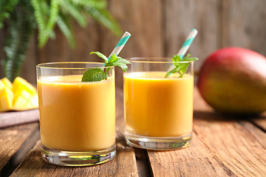 Fresh delicious mango drink on wooden table