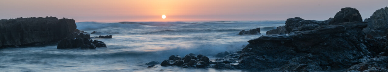 Beautiful beach at sunset with black volcanic rock - travel concept