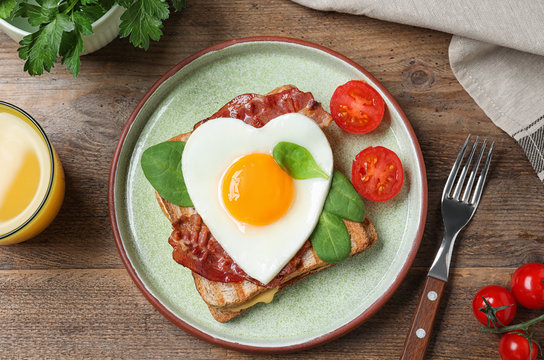 Tasty sandwich with heart shaped fried egg and bacon on wooden table, flat lay