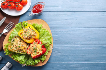 Tasty stuffed bell peppers served on blue wooden table, flat lay. Space for text