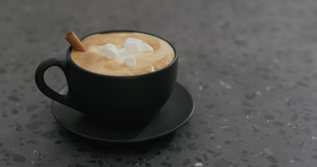 cappuccino with marshmallow and cinnamon in black cup on terrazzo countertop