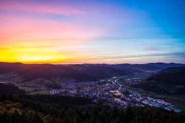Germany, Magical sunset sky over black forest village haslach im kinzigtal houses,streets,cityscape illuminated by night, aerial view from above with colorful unreal red sky,a perfect nature landscape