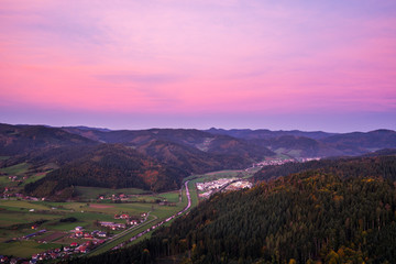 Germany, Red afterglow sky after sunset, aerial view above kinzigtal valley village and tree covered mountains in autumn season