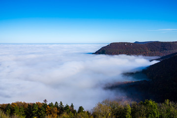Germany, Magical aerial view above endless lake of clouds in valley of swabian jura nature landscape on sunny day with blue sky near stuttgart