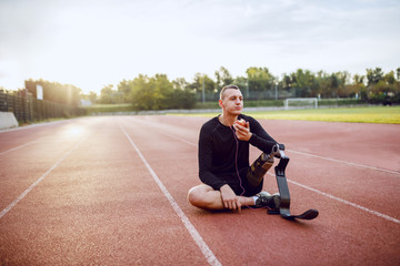 Fotomurales - Handsome caucasian sporty handicapped young man in sportswear and with artificial leg sitting on racetrack, listening music and eating apple.