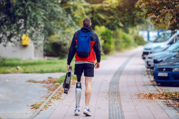 Fotomurales - Rear view of sporty caucasian handicapped man with artificial leg, in sportswear and backpack walking on the street. In hands is artificial leg.
