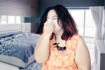 Fat woman resting in her bed while catching a cold