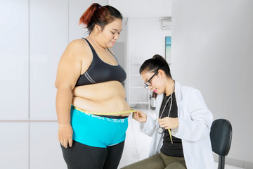 Fat woman visiting her doctor to have measurement